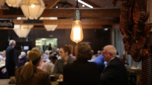 Edison light bulb hanging in busy retsuarant stock video imag