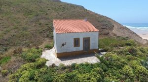 flying over a little old house on a beach cliff gallery image