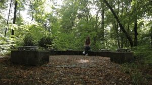 Girl sitting in forest in circle of seats