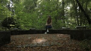 girl sitting in forest alone 2